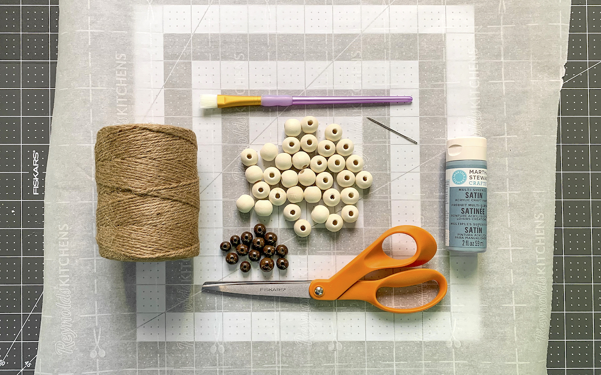 Twine-unfinished-wood-beads-scissors-paintbrush-blue-paint-and-a-needle