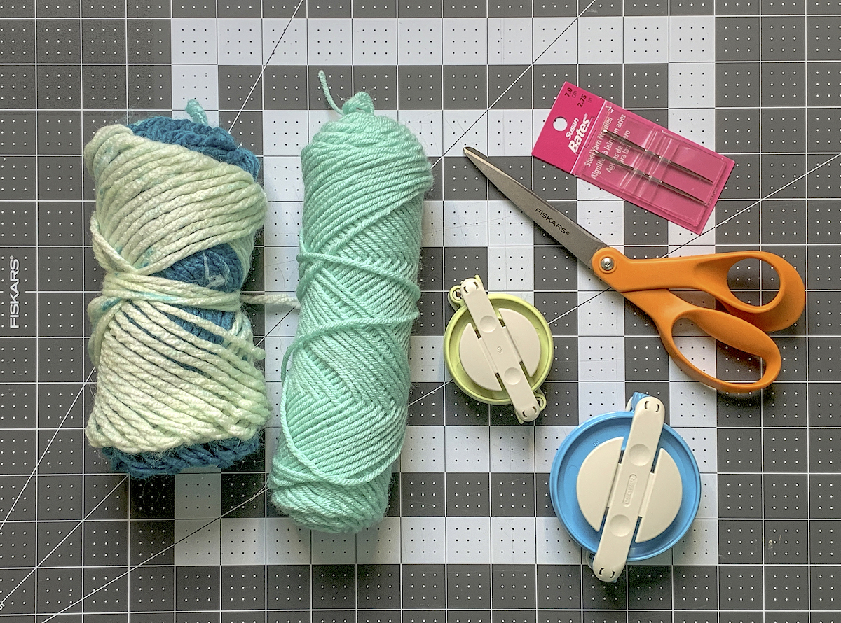 Two skeins of yarn with pom pom makers scissors and needles