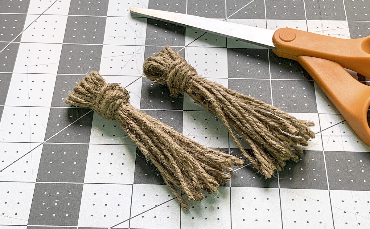 Two twine tassels laying on a craft mat with a pair of scissors