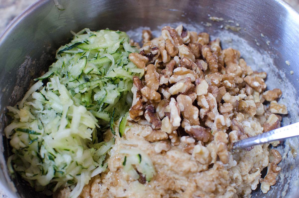 Bowl with zucchini bread batter zucchini and walnuts