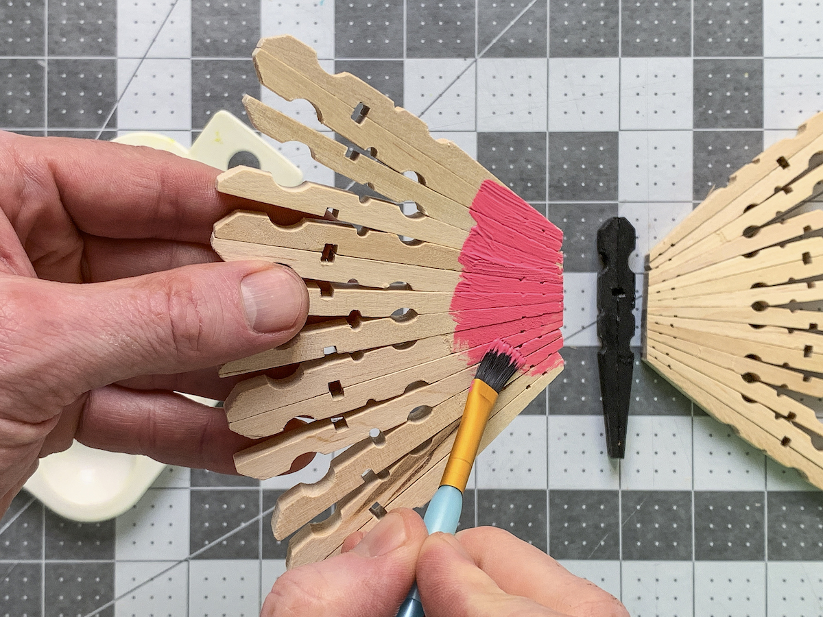 Painting clothespin wings with pink acrylic paint