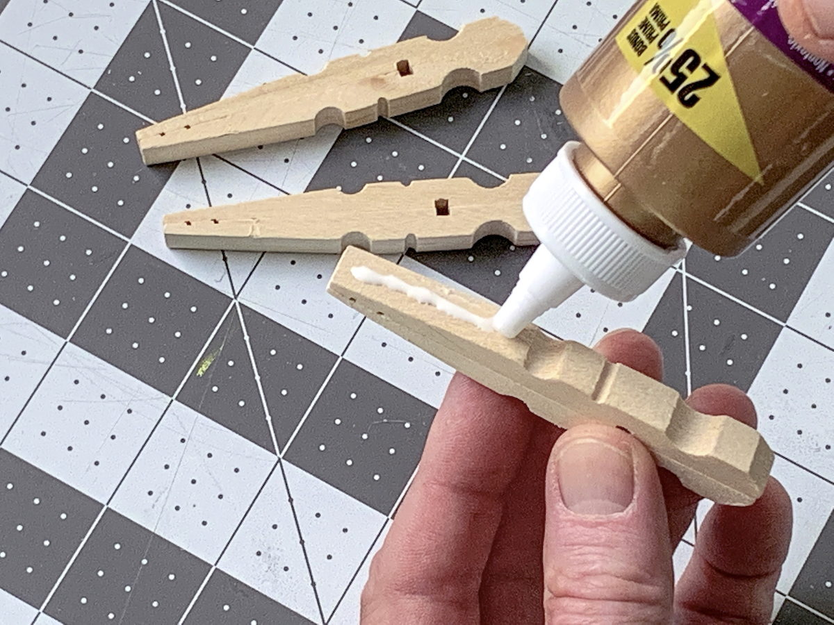 Adding glue to one side of a clothespin