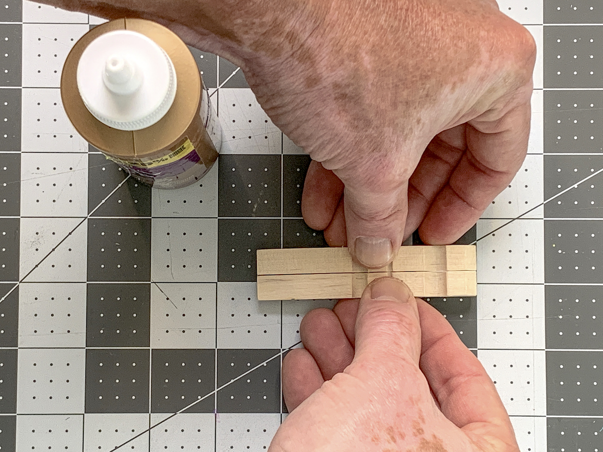 Hand holding two clothespins together with glue