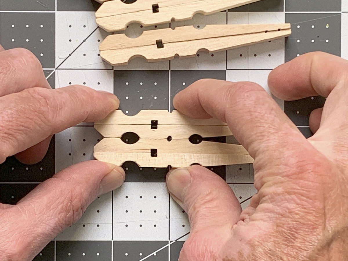 Hands holding two clothespins glued together