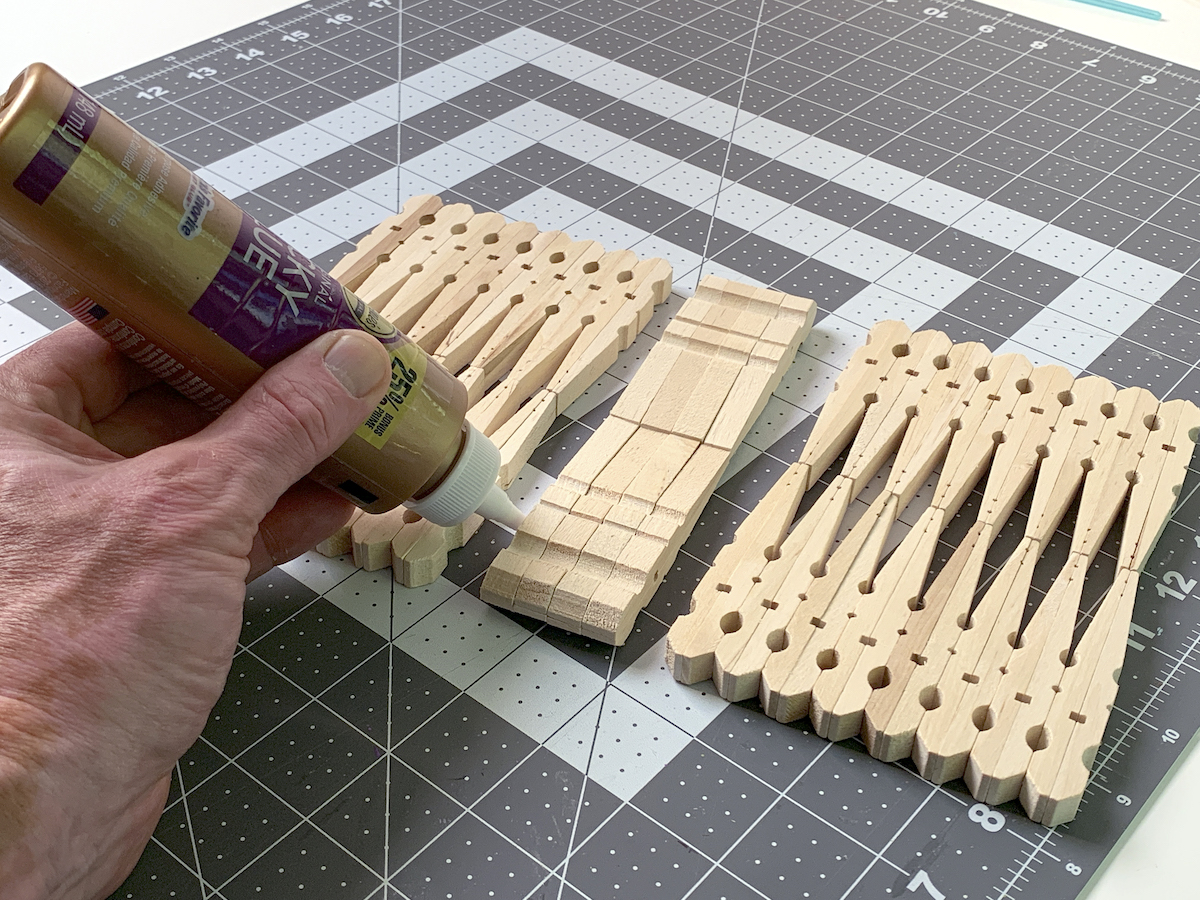Placing glue on one end of the clothespins