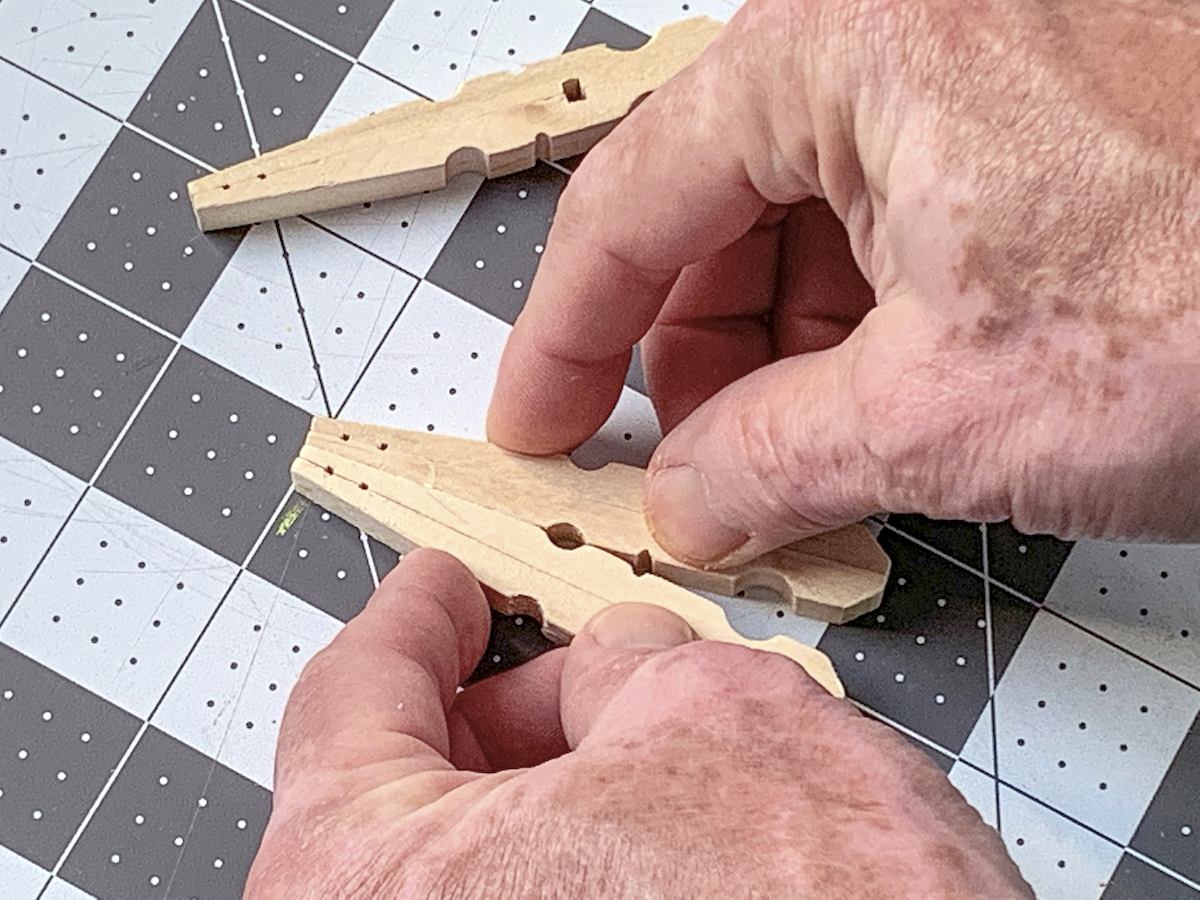 Pressing two clothespins with glue on them together